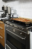 A baked pizza on a stainless steel gas cooker against a white wall