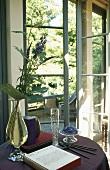 Beistelltisch mit Blumenvase und Buch neben offener Terrassentür