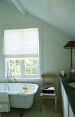 A bathroom with an antique bathtub under the window with a half-closed blind