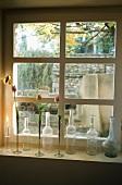 Stillleben auf Fensterbank - alte Flaschen und Vasen mit Blumen vor Sprossenfenster