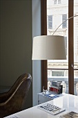 A white lampshade above a table and a window with a view