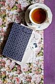 Tasse Tee neben Buch mit gemustertem Einband auf Papier mit Blumenmuster