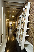 A corridor with a designer bookshelf against a brick wall