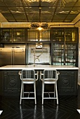 A traditional, open-plan kitchen with metal bar stools and artificial lighting