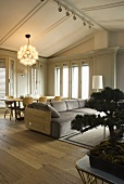 Sofa and dining area with hanging lamps in a living room with bright gray wood paneling