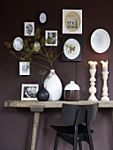 Ceramic vases and candlesticks on a rustic wall table in front of a dark-red wall
