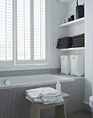 Bathtub with gray mosaic tiles in from of a window with closed blinds