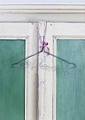 Coat hanger hanging on a wardrobe door