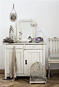 Bird cage in front of chest of drawers (country house style) with mirror