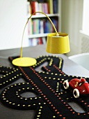 Yellow floor lamp and toy car with a playmat