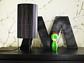 Table lamp with black shade and green toy on a black surface