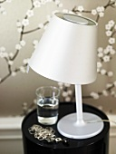 Table lamp with stainless steel shade on a black stool in front of patterned wallpaper