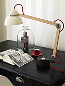 Table lamp with a porcelain shade and adjustable arm on a black surface
