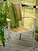 Throw on a garden chair with metal frame and wood seat and backrest in front of a rattan screen
