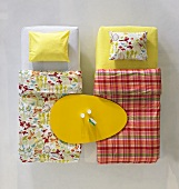 Easter in a showroom - egg shaped dinner plate on two beds with patterned bed linen