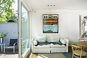 White sofa along a wall and open sliding patio door with a view of the patio