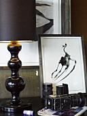 Table lamp with black shade and base next to a camera and framed picture