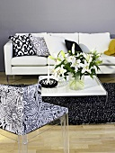 Flower bouquet on a coffee table with patterned chair and white sofa in front of a gray wall
