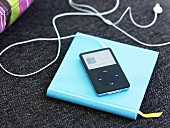 MP3 player with earphones on a turquoise cover of a book