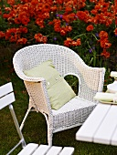 White wicker chair in front of a red flower bed