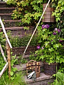 A flight of stone steps with flowers in wicker baskets and garden tools