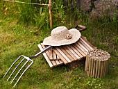 Wicker ladies hat on wooden tiles and pitchfork in the garden