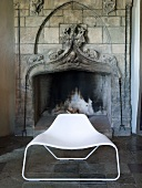 White shell chair in front of an old fireplace in a castle