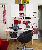 Arbeitsplatz mit schwarzem Drehstuhl vor weißem Schreibtisch und Hängeschrank mit Ablagen