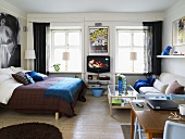 Bedroom with a double bed and sofa with coffee table in front of windows with a table lamp