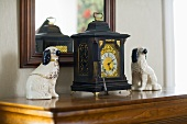 Antique clock and ceramic dog figurines in front of a framed mirror