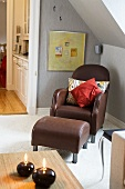 Leather chair with pillows and matching foot stool under a pitched roof