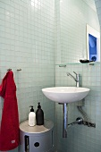 Designer wash basin with mirror in front of glass tile in a bathroom corner
