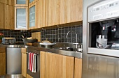 Kitchen cabinets with wood cabinet doors and black wall tiles