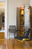 Cabinet with metal doors and interior lighting next to a chair with metal frame in designer style