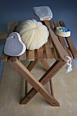 A bath sponge, soap, a pumice stone and brushes on a stool