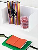 weiße Wandkonsole mit bunten Stiftboxen in Zylinderform und Hefte mit farbigem Einband