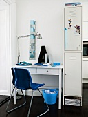 Desk and blue plastic shell chair next to a white locker