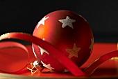Rote Christbaumkugel mit weissen Sternen und Band