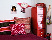 Corner in a children's room with colorful pillows on the bet and red metal cabinet with drawers