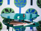 A toy figure and coloured pencils on a curved table made of shiny green metal