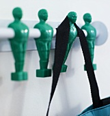 Black shoulder strap on a wardrobe rod with green men