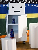 White rolling storage container with open door and a view of toys and white side table in front of a colorful wall hanging
