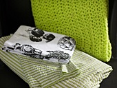 Tablecloths with country house style motifs and striped bed linen next to a green knitted scarf
