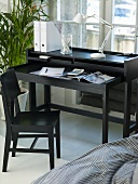 Designer secretary made of black wood with designer desk lamp and black wooden chair in front of a window