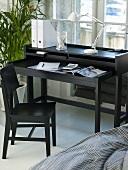 Designer Sekretär aus schwarzem Holz mit Designer Schreibtischlampe und schwarzem Holzstuhl vor Fenster