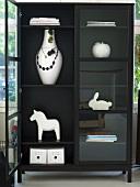 Modern black display cabinet with white knickknacks