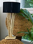 Table lamp with black shade and base out of natural wood sticks in front of wickerwork in the shape of a ball