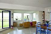 Offener Wohn- und Essraum mit weisser Holzverkleidung und blaue Stühle am Esstisch, Korbmöbel im Erker