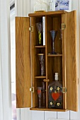 Wooden wall cupboard with open doors and view of stemware and glass bottles inside