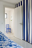 Room with blue and white striped curtain and open door with a view into the foyer